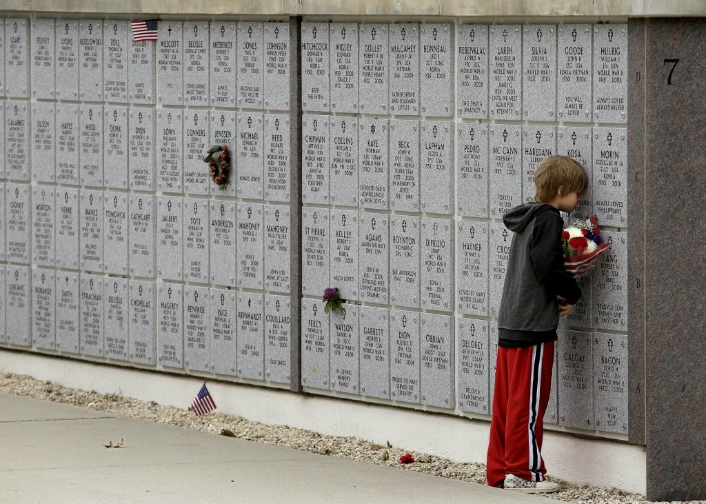 Charles Kosa III rests his head against the columbarium of his grandfather, Vietnam veteran Charles Kosa Sr., on Veterans Day at the Massachusetts National Cemetery in Buzzards Bay, Massachusetts. (Stephan Savoia/Associated Press)